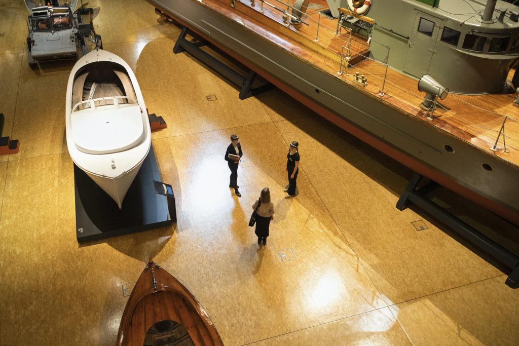 Kolme henkilöä seisoo museon näyttelytilassa