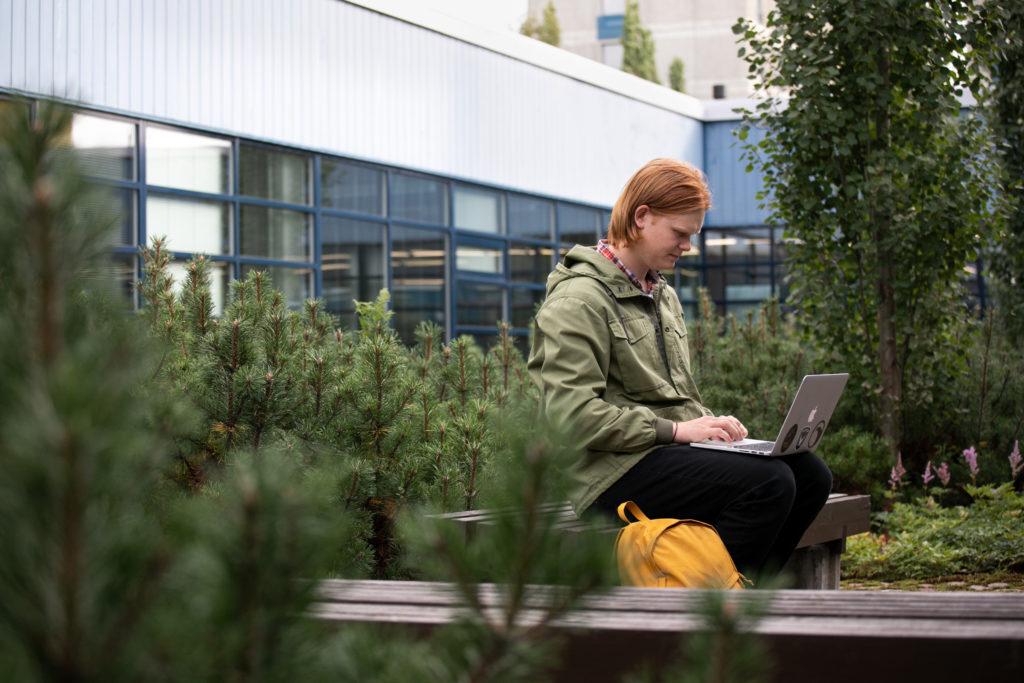 Yliopiston vehreällä kampuksella ulkona istuu miesoletettu opiskelija, joka opiskelee tietokoneellaan.