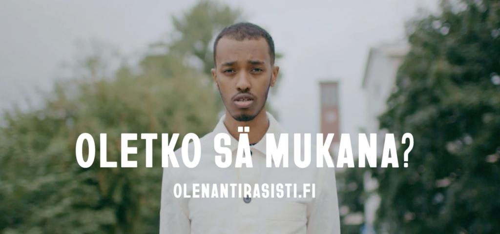 """Kuvassa tummaihoinen miesoletettu kesäisessä kaupunkimaisemassa. Kuvassa kysymys """"Oletko sä mukana?"""" sekä kampanjan verkkosivujen osoite olenantirasisti.fi."""